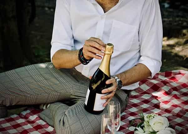 hombre abriendo botella de champagne picnic
